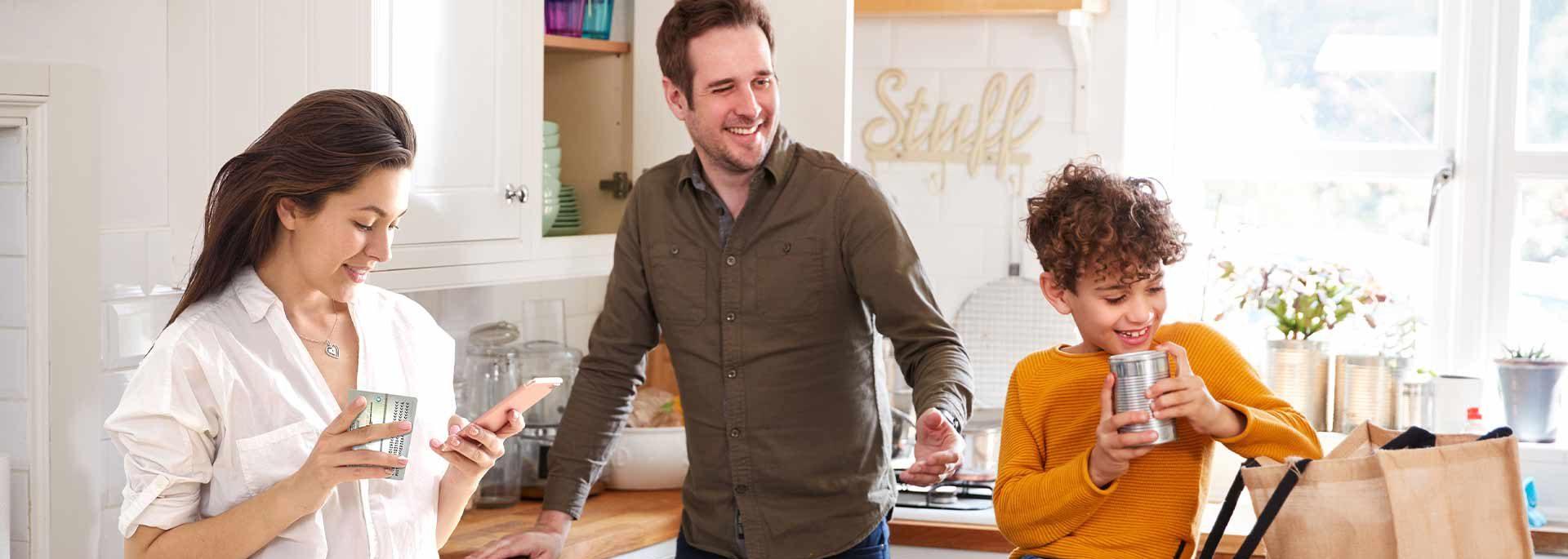 Familie in der Küche, Frau mit Smartphone